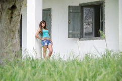 Bulgarian model wearing blue shirt and jean shorts. Cute lady with slim body wearing blue short shirt and jean shorts standing against house column looking away royalty free stock image