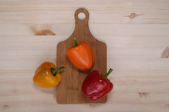 Bulgarian peppers on the table with a cutting board. Bulgarian peppers on a wooden table with a light texture Stock Photos