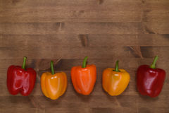 Bulgarian peppers on the table. Bulgarian peppers on a wooden table with a moderately dark texture Royalty Free Stock Photo
