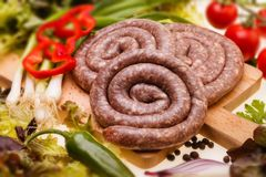 Bulgarian, raw sausages with vegetables on wooden board Royalty Free Stock Image