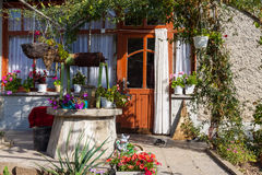 Bulgarian traditional farmyard. Rural yard with many flowers and well Royalty Free Stock Photography