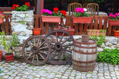 Bulgarian traditional street view with old wheel and wine barrel. Bulgarian traditional street view with old wheel, flowers and wine barrel stock images