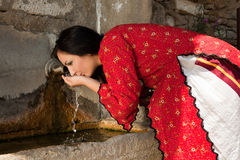 Bulgarian traditional well. Beautiful woman in traditional national bulgarian costume drinking at a well in the old village of Jeravna Royalty Free Stock Photos