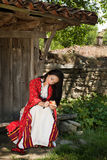 Bulgarian woman in national costume. Eating an apple in the old village of Jeravna Royalty Free Stock Photos