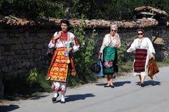 Bulgarian Women in Traditional Dress. Bulgarian women wearing traditional Bulgarian costumes walk down the street in Arbanasi, Bulgaria, on July 22, 2016 Stock Photo