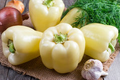 Bulgarian yellow pepper with vegetables onion, garlic and dill on a wooden background Royalty Free Stock Photos