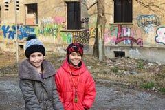 Bulgarisches Mädchen und ein Zigeunerjunge spielen zusammen vor ruiniertem altem Wohngebäude Stockfotos