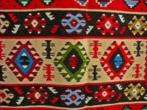 Bulgarisches traditionelles Volksteppichgewebe mit geometrischen Motiven und hellen Farben Stockfotos