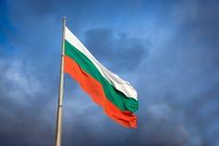 Bulgarisk flagga mot en molnig blå himmel Fotografering för Bildbyråer