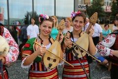 Bulgarisk grupp av flickor i traditionella dräkter på den internationella folklorefestivalen för barn och guld- fisk för ungdom Arkivbilder