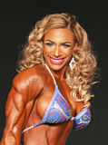 Bulging Latina Beauty Bust-Out Bodybuilding Champion. Curvy, bulging, buff bodybuilder Nicole Gutierrez competes in the Women's Physique competition finals Royalty Free Stock Photos