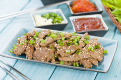 Bulgogi. Korean grilled marinated beef served with green chillies, garlic, ssamjang, kimchi and lettuce leaves Stock Image
