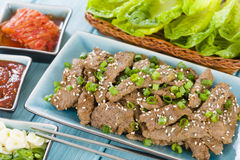 Bulgogi. Korean grilled marinated beef served with green chillies, garlic, ssamjang, kimchi and lettuce leaves Stock Photos