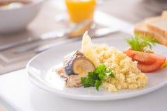 Bulgur avec des légumes et des rouleaux de poissons cuits au four avec le maïs, les tomates et le citron d'un plat blanc photos stock