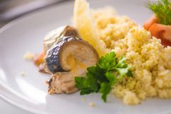 Bulgur com vegetais e rolos de peixes cozidos com milho, tomates e limão em uma placa branca imagens de stock