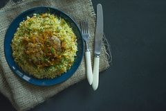 Bulgur with cutlet and vegetables served on a plate. Pork cutlets with porridge. Proper nutrition. Dark background. View from royalty free stock image