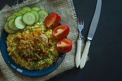 Bulgur with cutlet and vegetables served on a plate. Pork cutlets with porridge. Proper nutrition. Dark background. View from royalty free stock images