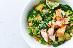 Bulgur with green vegetables and poached salmon. Healthy homemade meal royalty free stock image