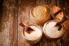Bulgur, quinoa and couscous. High angle of three rustic pots on a wooden background containing dried bulgur and couscous made from crushed durum and semolina Royalty Free Stock Images