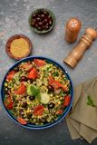 Bulgur tabouleh salad with vegetables. In a blue bowl. Top view on grey background Royalty Free Stock Photography