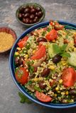 Bulgur tabouleh salad with vegetables in a bowl. Closeup bulgur tabouleh salad with vegetables in a blue bowl. Top view on grey background Royalty Free Stock Photo
