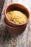 Bulgur wheat. In bowl on brown background royalty free stock image