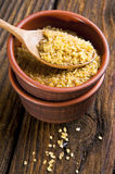 Bulgur wheat. In bowl with spoon on brown background royalty free stock image