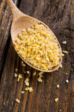 Bulgur wheat. In spoon on brown background stock images