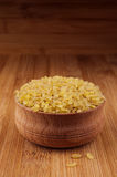 Bulgur in wooden bowl on brown bamboo board, close up. Rustic style, healthy dietary groats  background. Stock Photo