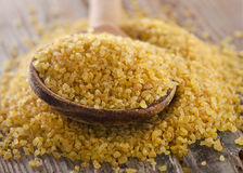 Bulgur in a wooden spoon on   wooden background. Stock Images