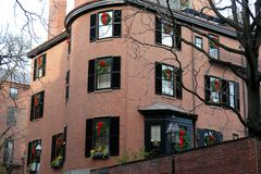 Buliding with christmas wreath in every window. Brick apartment building with chrsitmas wreaths hanging in every window Royalty Free Stock Image