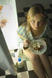 Is it bulimia?. Young woman eating cake beside fridge.She's looking at camera. High angle view Royalty Free Stock Photography