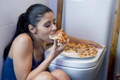Bulimic kvinna som känner sjukt skyldigt sammanträde på golvet av toalettbenägenheten på WC som äter pizza arkivfoton
