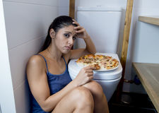 Bulimic woman feeling sick guilty sitting at the floor of the toilet leaning on WC eating pizza. Young sad and depressed bulimic woman feeling sick guilty Stock Photo