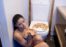 Bulimische Frau, die krankem schuldigem Sitzen am Boden der Toilette sich lehnt auf WC isst Pizza glaubt Lizenzfreie Stockfotografie