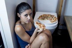 Bulimische Frau, die krankem schuldigem Sitzen am Boden der Toilette sich lehnt auf WC isst Pizza glaubt Lizenzfreie Stockfotos