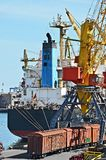 Bulk cargo ship and train under port crane Stock Photos