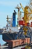 Bulk cargo ship and train under port crane Stock Photos
