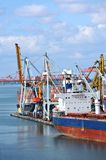 Bulk cargo ship under port crane Stock Image