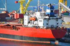 Bulk cargo ship under port crane Stock Photography