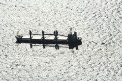 Bulk carrier cargo. Boat on silver sea, backlit stock photos