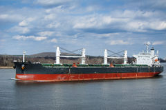 Bulk Carrier Cargo Ship Boat Sailing on River. Empty bulk carrier cargo ship with deck cranes sailing on a river calm water stock photography
