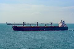 Bulk carrier cargo ship underway in sea. Laden bulk carrier cargo ship sailing along coastline royalty free stock photo