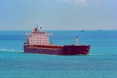 Bulk carrier cargo ship underway in sea. Laden bulk carrier cargo ship sailing along coastline stock images