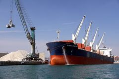 Bulk carrier Global Frontier docked and cleaning anchors. Bulk-carrier Global Frontier cleaning anchors box docked in the port of Alicante. Bow view with steel royalty free stock photos