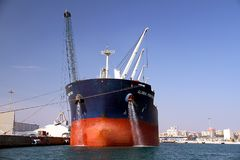 Bulk carrier Global Frontier docked and cleaning anchors. Bulk-carrier Global Frontier cleaning anchors box docked in the port of Alicante. Bow view with steel Stock Images