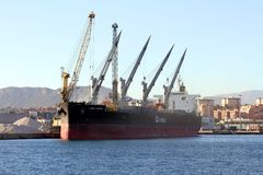 The bulk-carrier LAWIN ARROW loading cement with cranes in the port of Alicante. High cranes loading of cement a big bulk-carrier vessel docked in the port of Royalty Free Stock Photos