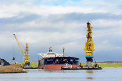 Bulk carrier Martine is being discharged by cranes. Stock Photography