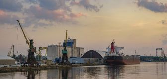 Bulk carrier moored at the quay, and busy with cargo operations. royalty free stock image