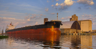 Bulk carrier moored at the quay, and busy with cargo operations. stock image